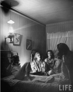 Young girls sitting on beds and talking by light of kerosene lamps. New York, 1945. By Nina Leen