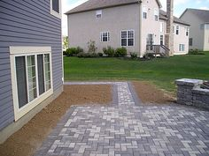 This simple driveway design harmonizes perfectly with the color of the home and provides a simple walkway around the house. Beautiful work by the Paverstone Design Group.