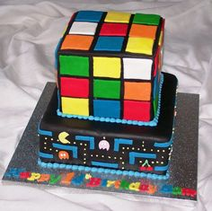 My sons birthday cake, 80's inspired, with pacman design on bottom cake, topped with a rubix cube cake.