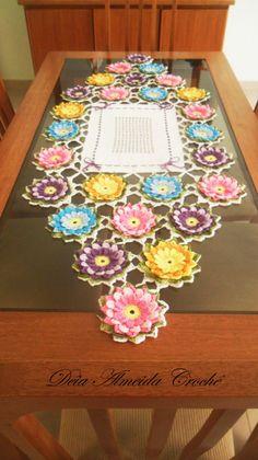 Caminho de mesa em crochê com flores em amarelo, rosa, lilás e azul, folhas verde multicolorido e fundo branco.  Pode ser feito em outras cores e tamanhos.