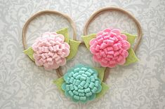 Pick your favorite! These pretty button mums are available in your choice of pink, aqua mist and pale pink felt! They measure 3 inches wide with the leafs and are attached to a nylon one size fits most (newborn to child) band. Pretty year round! Please remember that you are purchasing