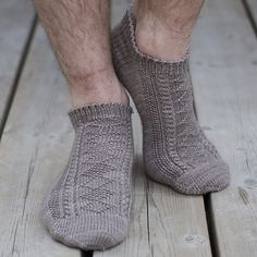 These socks are inspired by the Flamborough Ganseys. They feature an alternating diamond panel down the front and a chevron panel down the back, flanked by cables and a wraparound seed stitch panel.