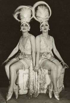 The Dolly Sisters: Rosie and Jenny   (Rosika and Yansci) wearing the costumes of showgirls with ostrich feather headdresses, sitting on a low dresser, holding hands, in a dance revue in Paris in 1923