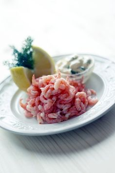 A plate of freshly-peeled danish fjord shrimps with a slice of lemon.