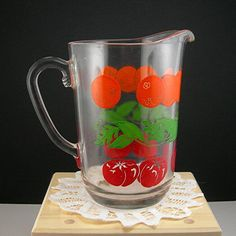 ➤ Vintage 1950s mid-century clear glass juice pitcher ➤ Colorful enameled oranges and tomatoes and greenery on the outside ➤ It holds 4 cups or 32 of juice or liquid ➤ Measures 7 tall and 4-1/2 wide (not including spout or handle). ➤ Heavy, thick glass...well made ➤ Great piece for decorating your
