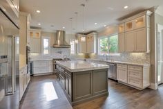 Transitional Kitchen with Kitchen island, Flat panel cabinets, Crown molding, Pendant light, Hardwood floors, Flush, U-shaped