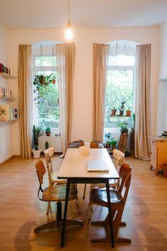 Einrichtungsidee für einen gemütlichen Essbereich: Tisch mit vier verschiedenen Holzstühlen für Vintage-Charme, große Fenster, viel grüne Bepflanzung - fertig ist ein gemütlicher Essbereich.  2-Zimmerwohnung in Berlin.