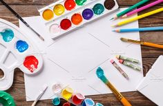 Paper, watercolors, paint brush and some art stuff on wooden   table by Supermne on @creativemarket