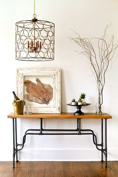 ring chandelier, coral art, antique gold ice bucket, antique black metal platter, wood and pipe console table www.10madedesign.com