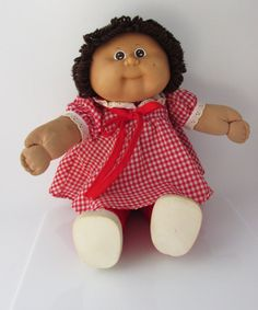 Vintage 1980s brunette Cabbage Patch Kid with a soft body. She wears a red gingham dress, red leggings and white shoes. Condition: Very good