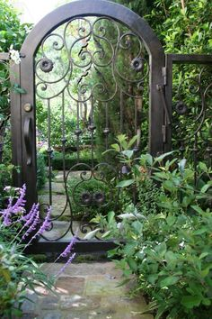 Lovely arched metal gate & the plantings are great too.