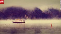 A traditional wooden boat, called a pletna, crosses Lake Bled amidst the morning fog.