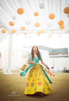 Light Lehengas - Yellow Lehenga with Scattered Red Print and Aquamarine Blue Choli and Dupatta with Orange Tassels | WedMeGood #wedmegood #indianbride #indianwedding #indian #lehenga #yellow #aqua #bridal