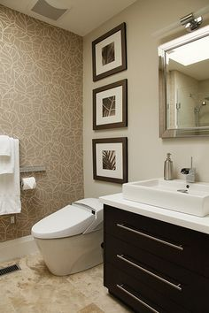 The travertine floor tile, the wallpaper,  the high tech toilet,  the dark cabinet --- LOVE this bathroom