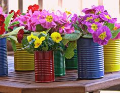 DIY centerpiece for spring using potted plants. Just pop the plant into the prepared container. Cans can be decorated in any way- think color, paint, ribbon, burlap, paper, embellishments, the options are endless.