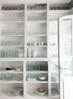Floor-to-ceiling shelves holding a collection of glassware and china | Lonny.com