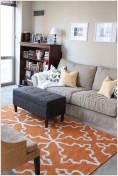 Khaki / tan couch with orange and grey accents. IDEA: Same colouring's for our bedroom. Paint walls grey, dark furniture, white linen, orange accents and rugs.