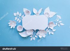 Festive flower composition with white paper flowers with greeting card on the blue background. Flat lay, overhead view, top view