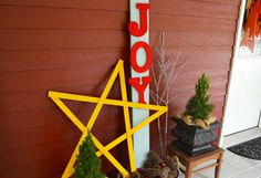 A bright yellow star ties together this holiday porch decor. This easy project begins with five Home Depot yardsticks, painted yellow and fastened together with a staple gun. Get more small space Christmas decorating ideas at the Garden Club.