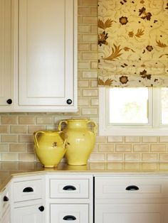 The red, yellow and white floral print of this roman shade makes a vibrant graphic statement in the kitchen. Pale yellow backsplash tile and lemon yellow pitchers help add to the sunny feel.