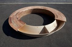 new york-based designer louis lim has integrated a hidden storage unit into a circular bench for 'round'. the wooden furniture piece  is in the form of a semicircle, as the solid wooden boards conceal a continuous triangular drawer. when one side is pushed, the opposite end  reveals the central hollow parts. the hidden compartment rotates all around, showing one section at a time, until it is once again swallowed