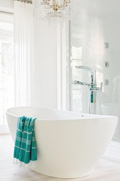 A crisp white and coastal blue color palette and opulent amenities make the master bathroom the most luxurious room in the house.