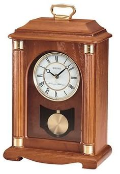 The Seiko Pendulum Mantel Clock is a Dark brown solid oak Carriage style clock with glass crystal and brasstone accents. Westminster/Whittington quarter-hour chime w/ Nightime Chime Shutoff option. Size: H W 9 D 5