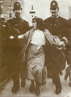 """BAD REPUTATION identifies the woman in the iconic photo: """"on the front page of the Daily Mirror: a young woman, flanked by a pair of police officers. Her skirts and shawl are in disarray, her hair wild. She appears to be shouting. Her name is Dora Thewlis, a weaver in a Huddersfield mill. She is just sixteen years old."""" Read her story."""