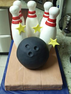 Ten Pin bowling Cake - Chocolate mud cake with chocolate ganache. The pins are plastic toy pins covered in fondant. The bowling ball was made using the small Wilton ball tin! Thanks for looking.