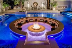 HGTV presents a tropical pool that with a sunken fire pit seating area and surrounded by stone pavers. It includes an ipe wood walkway and an in-wall fire feature.