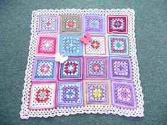 Pretty & dainty - like the DC around the granny squares.  Squares in block stitch would look great too.   #crochet #granny_square #edging