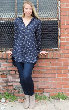 Teton – Navy Fleur by CP Shades  Pull on tunic top with open front placket, pointed collar & long sleeves. Back yoke with slight gathering. Button cuffs & curved shirt tail hemline. Front patch pockets. Mid to light weight linen. Printed with dainty khaki colored flowers & tiny dots.