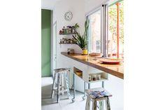 La cocina con una barra apoyada en los amplísimos ventanales que rodean el patio..  /Magalí Saberian