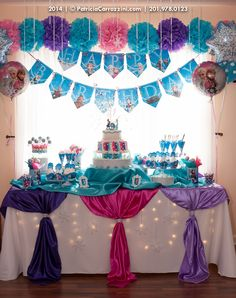 Frozen Birthday Party, cake table idea. Frozen birthday banner and pom poms.