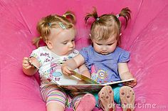 Two toddler girls sitting together in pink chair, reading a storybook together.