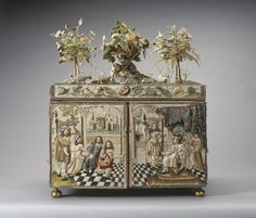 A stumpwork casket with two doors and brass drop handles and interior fitted with mirror and small drawers.Top decorated with sheperdess wearing a hat with four sheep, a lamb and a dog, sitting under an oak tree. Presented to Queen Mary by Lord Plender (1861-1946) in 1932 | Royal Collection Trust