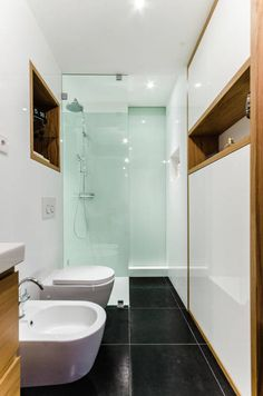 Ze względu na nietypowy kształt pomieszczenia wszystkie urządzenia ustawiono w szeregu, na końcu montując prysznic oddzielony od przestrzeni łazienki szybą, bez brodzika. Wszystkie potrzebne przedmioty mieszczą się na półkach we wnękach ściennych.