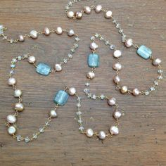 Beautiful rectangular coins of blue green kyanite are wrapped with pink freshwater keshi pearls and accented with moonstone rondelles.    The name,