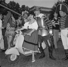 """Auf dem Pariser Fest der Motorroller (Fête parisienne du scooter): 150 Mitwirkende in historischen Kostümen aller Epochen (Figuren aus Geschichte, Literatur und Film), starten zu einer Fahrt von der Place de l'Étoile zum Jardin d'Acclimation; die Figuren der """"Esmeralda"""" aus dem """"Glöckner von Notre-Dame"""" und des """"Don Quijote"""" am Start. Foto, 5. Juni 1955."""