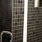 Your first impulse for a tiny bathroom might be lots of optic white. Instead, play up the close quarters with a darker hue.Black tiles a...