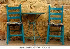 stock photo : Blue table and chairs against a yellow wall, in Greece