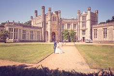 Bride and groom pose outside Highcliffe castle. Photography by one thousand words wedding photographers