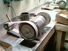 Belt Grinder by P Abrera -- Homemade belt grinder constructed from a bench grinder, contact wheels, and a metal base. http://www.homemadetools.net/homemade-belt-grinder-41