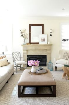 Cozy family room. Bright and white. Linen White paint by Benjamin Moore. Custom Ottoman. Original art. Geometric side chair. Soothing color palette.
