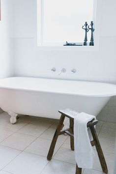 White and simple this bathroom is flooded with light. With a claw foot tub beneath a large white window, minimal decor keeps the space simple, practical, and uncluttered. A simple stool holds a towel and provides a space to sit or set your things.