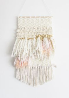 This stylish wall hanging is made by hand . Off white, peach, light pink, gold leaf, a lot of texture and a beautiful calming natural look. Gold leaf add an interesting texture and make this weaving unique. It hangs from a 12 wide wooden rod and is ready to hang. Due to the handmade process of this art form two weaves will never be exactly the same. The weaving itself measures 12 by 24 for a total of 35 long from where it hangs to the bottom fringe Ships within 3-5 days. This item is de...