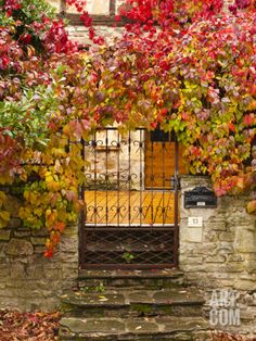 France, Midi-Pyrenees Region, Tarn Department, Cordes-Sur-Ciel, Gate with Autumn Foliage Photographic Print by Walter Bibikow at Art.com