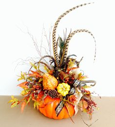 #Fall pumpkin arrangement with pheasant feathers.