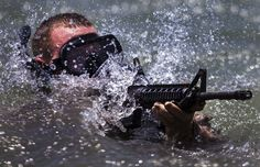 A US Raid Force Marine engages simulated hostile targets during an amphibious insertion for sustainment training.