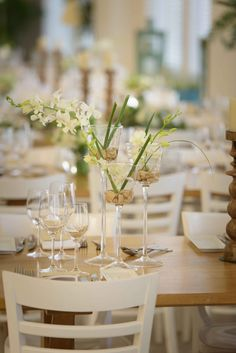Yahav Green - Tailor Made Design  Venue: housea Photo: Yulia Tokarev  A beautiful elegant white wedding decor.   white orchid, tulips and buttercup centerpieces.  Wooden tables and vintage candle lamp.